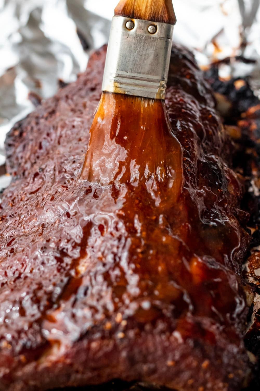 brushing bbq sauce on the ribs